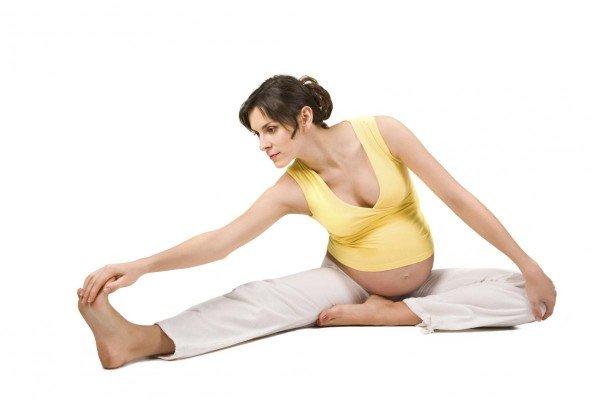 беременная девушка занимается пилатесом