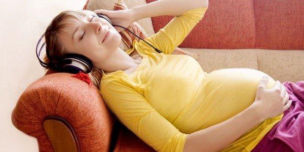 будущая мама расслабляется, слушая плеер