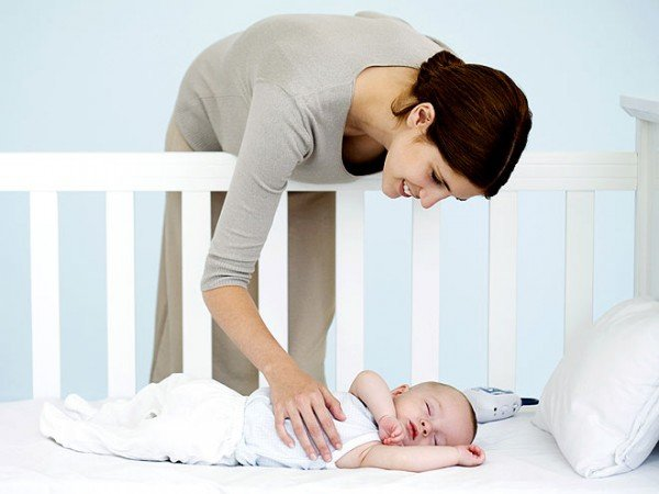 мама склонилась над спящим в кроватке малышом