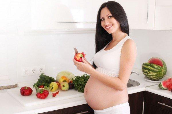 Беременная девушка чистит болгарский перец