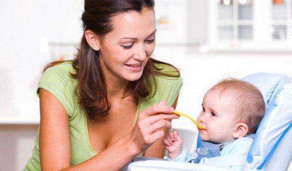 мама кормит малыша с ложечки