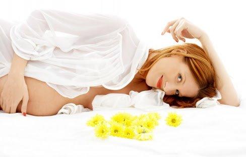 Беременная в белой рубашке лежит на кровати