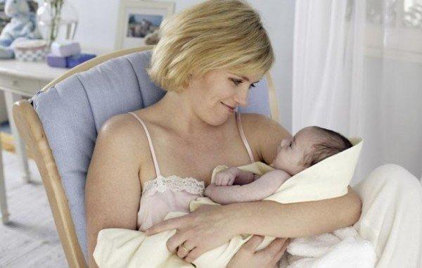 женщина держит на руках своего новорожденного ребенка