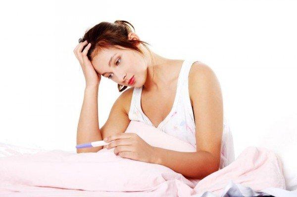 женщина озадачено смотрит на тест для определения беременности