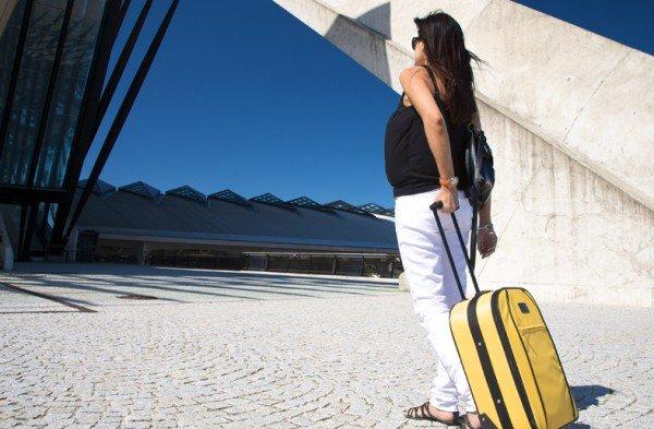 Беременная идет с дорожным чемоданом