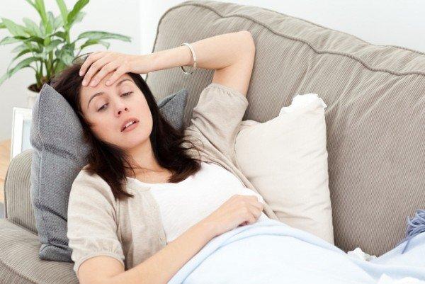 Приболевшая девушка лежит на диване