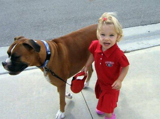 Маленькая девочка выгуливает собаку