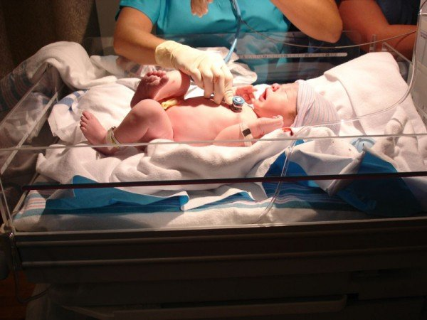Доктор обследует новорожденного ребёнка