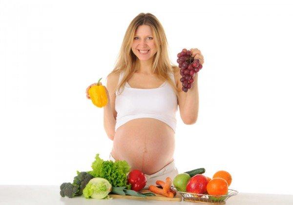 Беременная девушка с овощами и фруктами