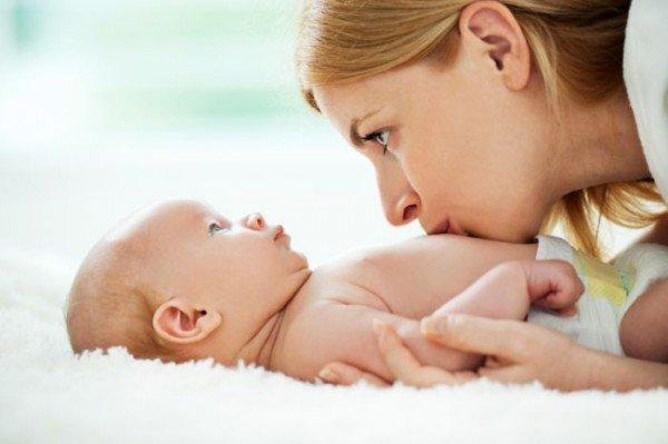 Мама целует в животик своего ребёнка