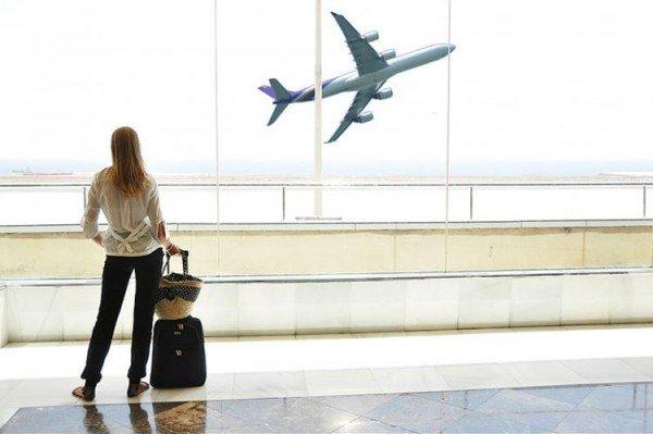 Женщина смотрит на летящий самолёт