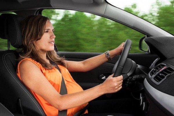 Беременная пристегнутая ремнём безопасности ведёт машину
