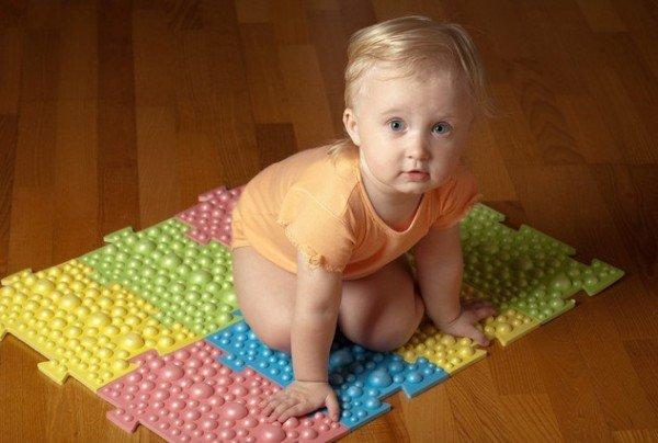 Ребенок сидит на ортопедическом коврике