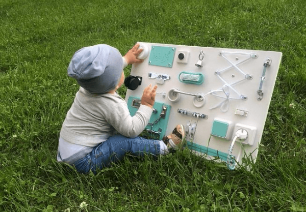 Ребёнок играет бизибордом