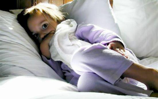 Девочка в страхе поджала ноги на кровати