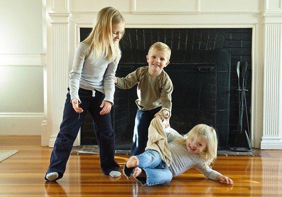 Две девочки и мальчик играют на полу возле камина