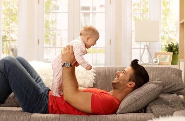 Малыш смеётся в ответ на улыбку папы