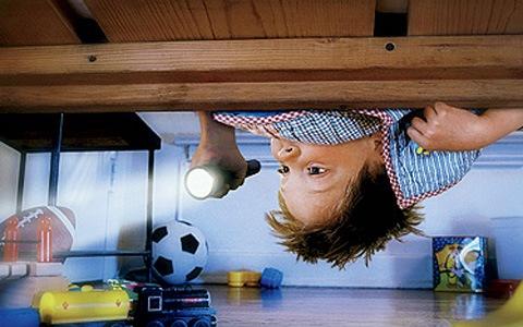 Мальчик с фонариком заглядывает под кровать