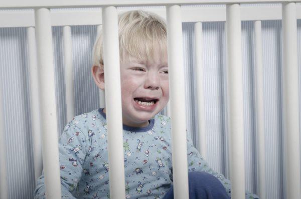 Малыш плачет в своей кровати