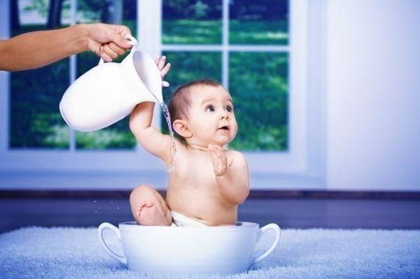Малыша поливают водой