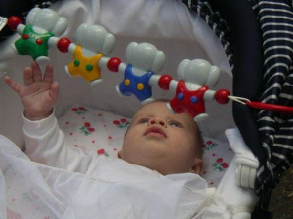 Над ребёнком в коляске размещены звонкие игрушки-погремушки