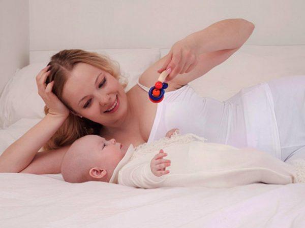 Мама предлагает ребенку взять в руку яркую погремушку