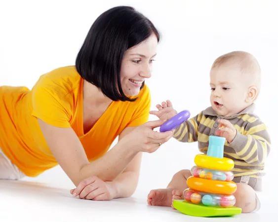 Малыш с помощью мамы уже собирает пирамидку