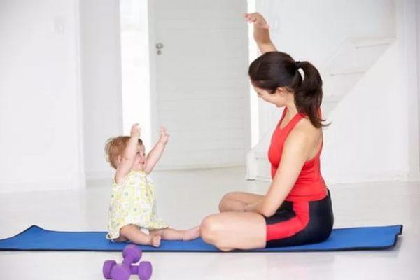 Малышка вместе с мамой делают зарядку