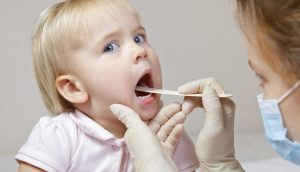 врач осматривает ребёнку горло