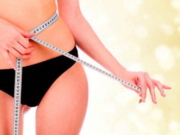 Женщина измеряет объём своей талией