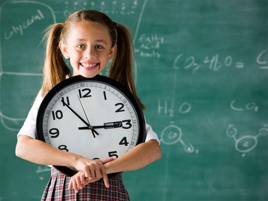 Девочка держит часы со стрелками, на заднем фоне доска с написанными на ней химическими формулами