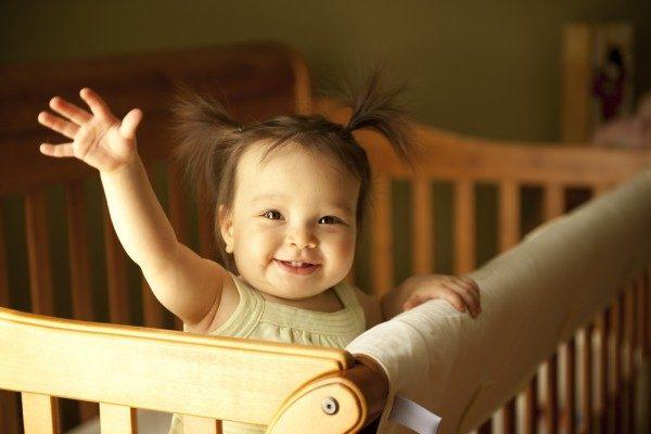 Девочка с хвостиками стоит в детской кроватке подняла ручку, улыбается