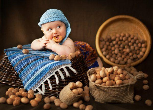 Грудной ребёнок сидит в лукошке среди грецких орехов