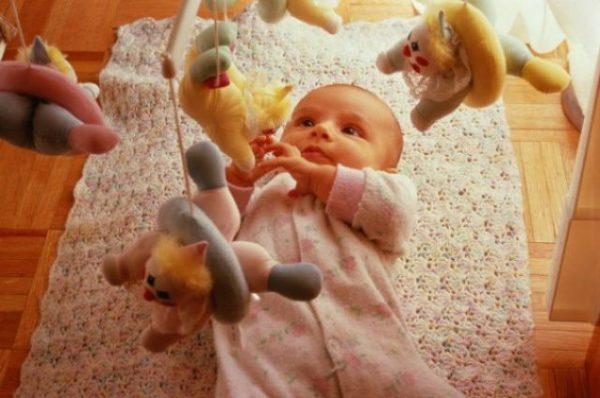 Малыш в кроватке играется мобилем