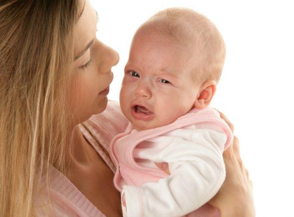 Мама держит плачущего малыша в розовом комбинезоне и белой распашонке