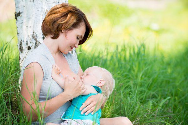 Мама кормит малыша летом