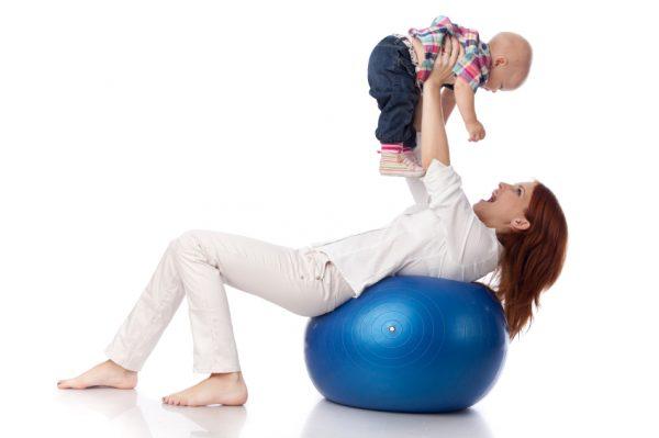 Мама с ребёнком занимаются фитболом