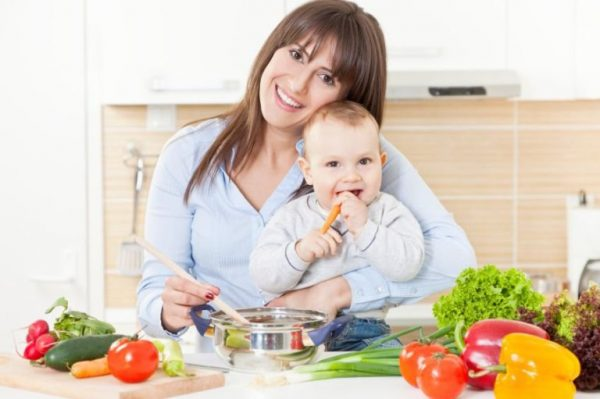 Мама с грудным ребёнком за столом со свежими овощами