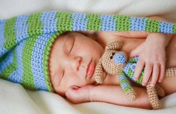 Ребёнок в полосатой шапочке с такой же полосатой игрушкой спит