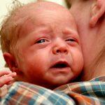 Малыш с опухшими глазами плачет, лежит на плече мамы в клетчатой рубашке