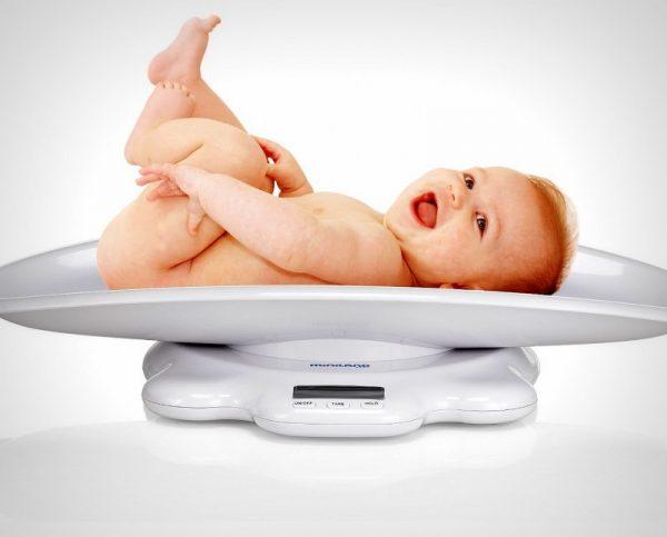 Ребёнок лежит на весах