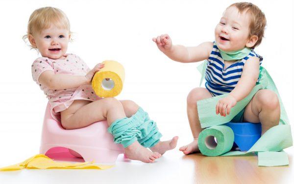 Девочка и мальчик сидят на горшках