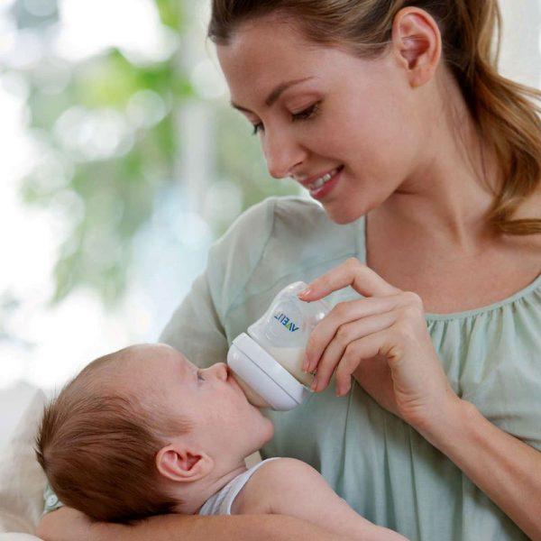 Женщина кормит младенца из бутылочки