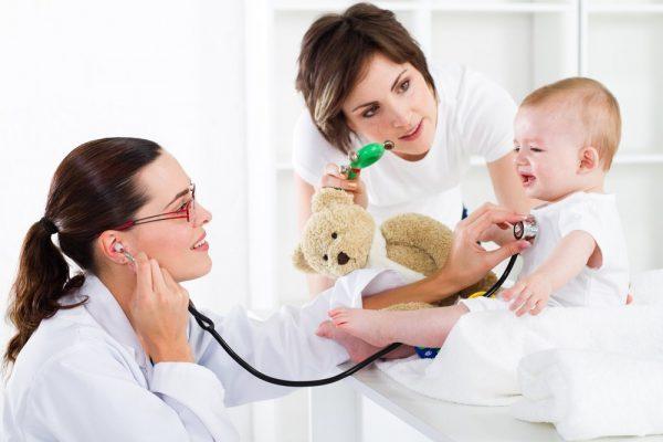Педиатр осматривает грудничка, мама отвлекает ребёнка игрушкой