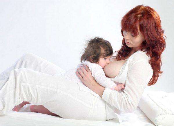 Мама кормит ребёнка полусидя