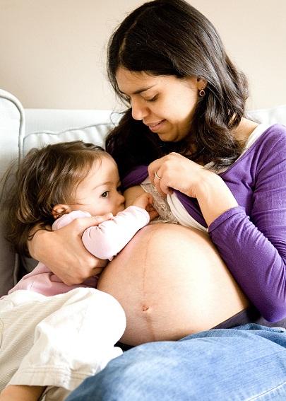 Беременная мама кормит ребёнка грудью