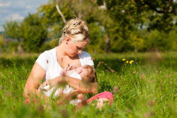 Мама кормит грудью в поле