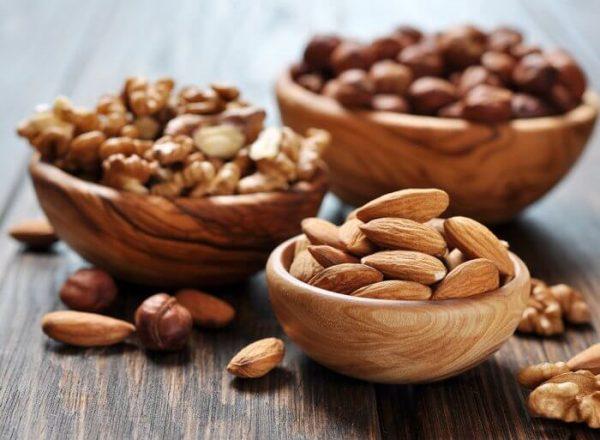 Три вида орехов в деревянных мисках на столе