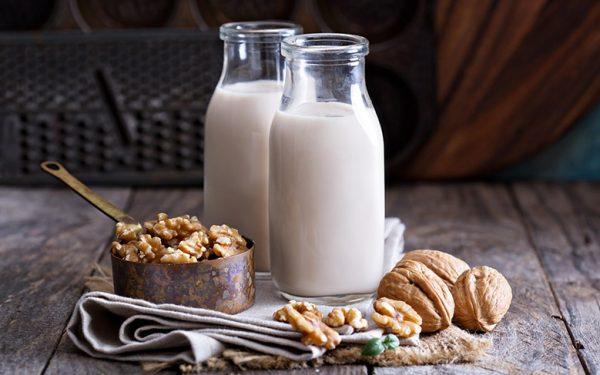 Грецкие орехи и две бутылки молока на столе