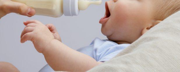 женщина кормит ребенка из бутылки